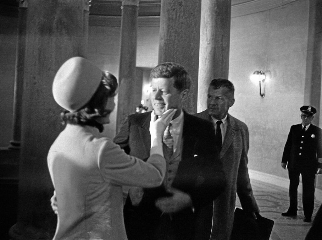 . Mrs. John F. Kennedy has a chuck under the chin for her husband moments after he became president, January 20, 1961.  This exclusive picture by AP photographer Henry Burroughs, was taken in the rotunda of the capitol just after President Kennedy left the inaugural stand.  (AP Photo/Henry Burroughs)