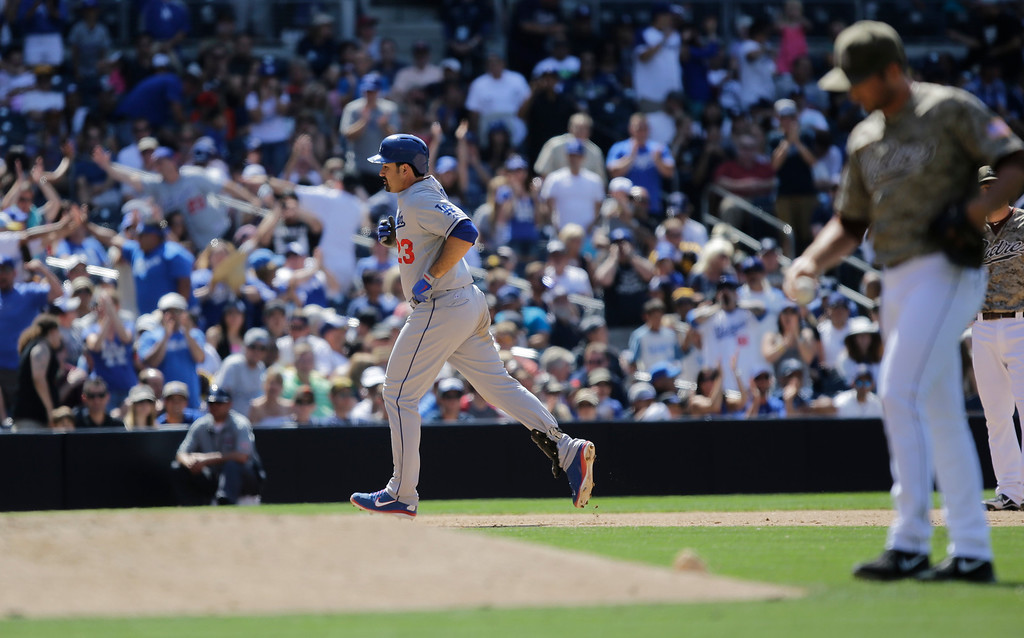 . Los Angeles Dodgers\' Adrian Gonzalez rounds third with his solo home run in the ninth inning as San Diego Padres  pitcher Huston Street stands behind the mound in a baseball game in San Diego, Sunday, June 23, 2013. (AP Photo/Lenny Ignelzi)