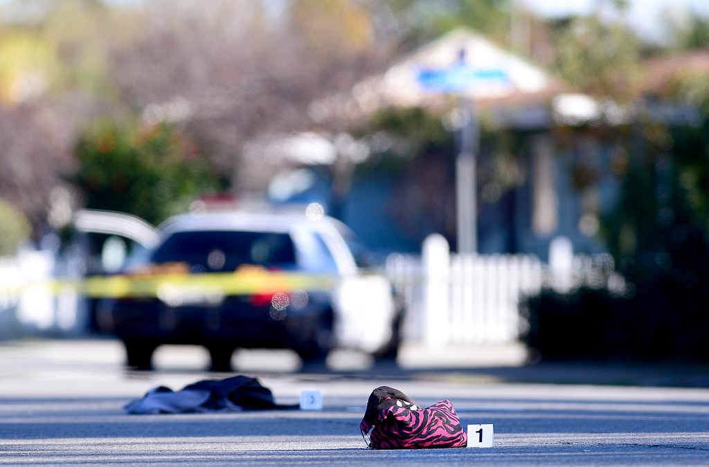 . A purse and clothes lay in the street as Pomona Police detectives investigate a shooting of a teenage girl in the 1000 block of Laurel Avenue in Pomona Saturday, November 30, 2013.  The city has been plagued by violence, with 27 homicides this year. Police are offering $10,000 rewards for information leading to conviction in any of this year\'s unsolved killings. (Photo by Sarah Reingewirtz/Pasadena Star-News)