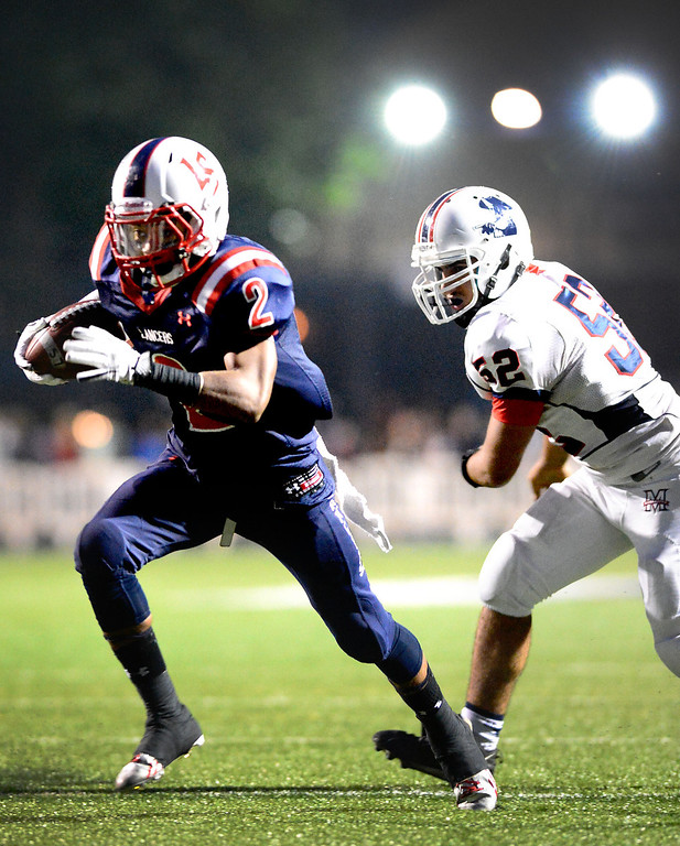 . Maranatha\'s Chris Ajalat (52) attempts to stop La Salle\'s running back Bryce Harvey (2) as he makes a touchdown during the first half of Friday night\'s prep football game at La Salle High School in Pasadena, on September 20, 2013. (Photo by Sarah Reingewirtz/Pasadena Star-News)