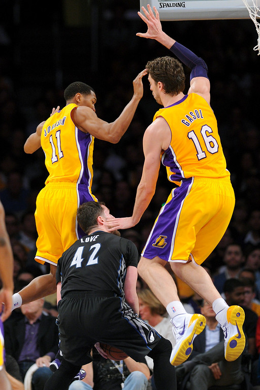 . The Timberwolves\' Kevin Love fakes the Lakers\' Wesley Johnson, left, and Pau Gasol near the hoop in the first half, Friday, December 20, 2013, at Staples Center. (Photo by Michael Owen Baker/L.A. Daily News)
