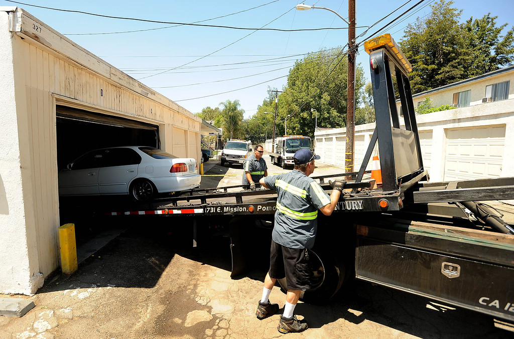 . A white Honda Civic is towed from the scene of a double-shooting along the 300 block of Orchid Lane in Pomona August 11, 2013.   GABRIEL LUIS ACOSTA/STAFF PHOTOGRAPHER.
