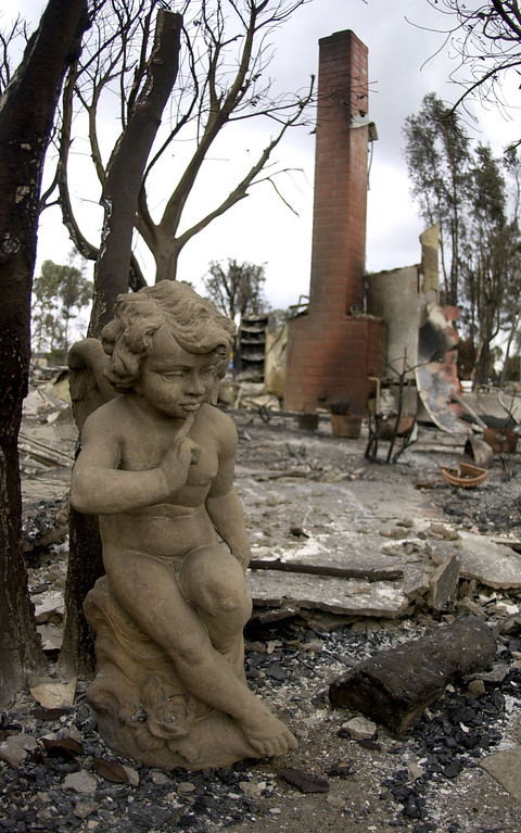 . A guardian angel statue remains in the charred backyard of a home in the Scripps Ranch area of San Diego, Calif. Thursday, Oct. 30, 2003. The home was among more than 1,500 lost in the 275,000 acre Cedar fire. (AP Photo/Charlie Riedel)