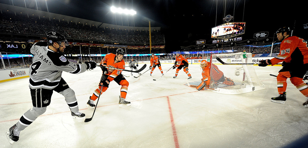 . Los Angeles Kings right wing Justin Williams (14) shoots past Anaheim Ducks\' Hampus Lindholm (47) in the first period of the inaugural NHL Stadium Series game at Dodger Stadium in Los Angeles on Saturday, Jan. 25, 2014. (Keith Birmingham Pasadena Star-News)