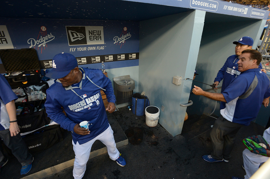 . Juan Uribe ducks away from Hyun-Jin Ryu as he takes a bug sprayer and shoots what his fellow players hoped was water, at them before the start of the game. The Dodgers played the San Diego Padres at Dodger Stadium. Los Angeles, CA. 8/20/2014(Photo by John McCoy Daily News)