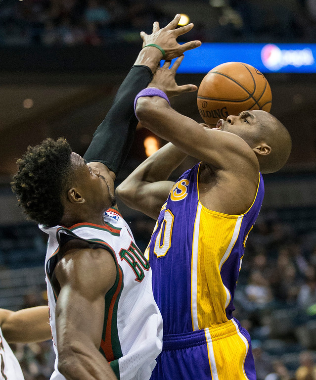 . Milwaukee Bucks\' Jeff Adrien can not stop Los Angeles Lakers\' Jodie Meeks on a drive to the basket during the first half of an NBA basketball game Thursday, March 27, 2014, in Milwaukee. (AP Photo/Tom Lynn)
