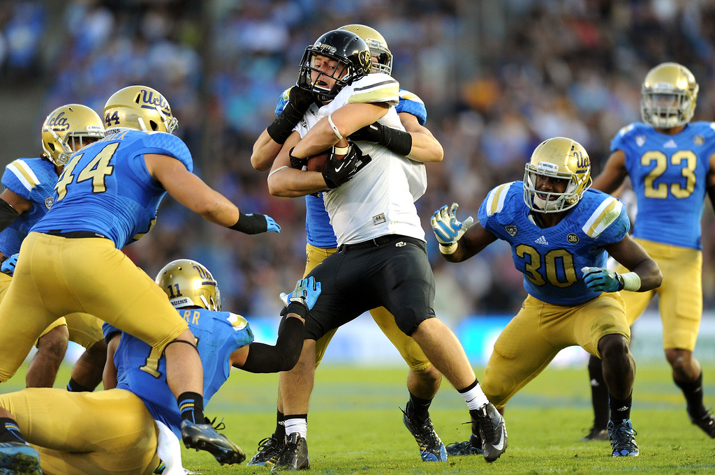 . The UCLA defense wraps up Colorado tight end Kyle Slavin, Saturday, November 2, 2013, at the Rose Bowl. (Photo by Michael Owen Baker/L.A. Daily News)