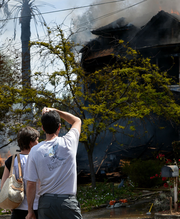 . Tim and Laurie McNaughton, comfort each other while their home burns. The home in the 1600 block of Olive Street, one of the city�s historic neighborhoods, was destroyed in a fire Wednesday April 9, 2014, according to fire officials. As they arrived, firefighters found the home, built in 1903, engulfed in flames and smoke billowing out of the structure. (Photo by Rick Sforza/The Sun)