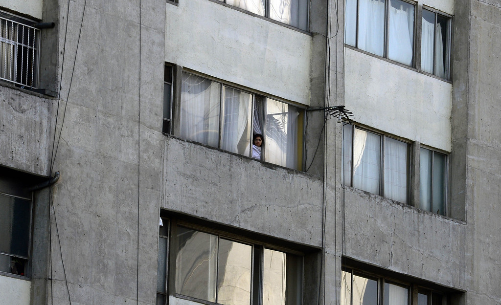 . A woman looks out from a window as people evacuate buildings after a strong earthquake rattled Mexico City on April 18 , 2014. A powerful 7.0-magnitude earthquake rattled Mexico City on Friday, swaying buildings, shattering windows and prompting people to rush into the street as power went out, authorities said. The National Seismology Service said the quake\'s epicenter was 31 kilometers (19 miles) northwest of Tecpan, in the southwestern state of Guerrero, near the Pacific resort of Acapulco. The US Geological Survey gave a higher measurement of 7.5-magnitude.           (ALFREDO ESTRELLA/AFP/Getty Images)