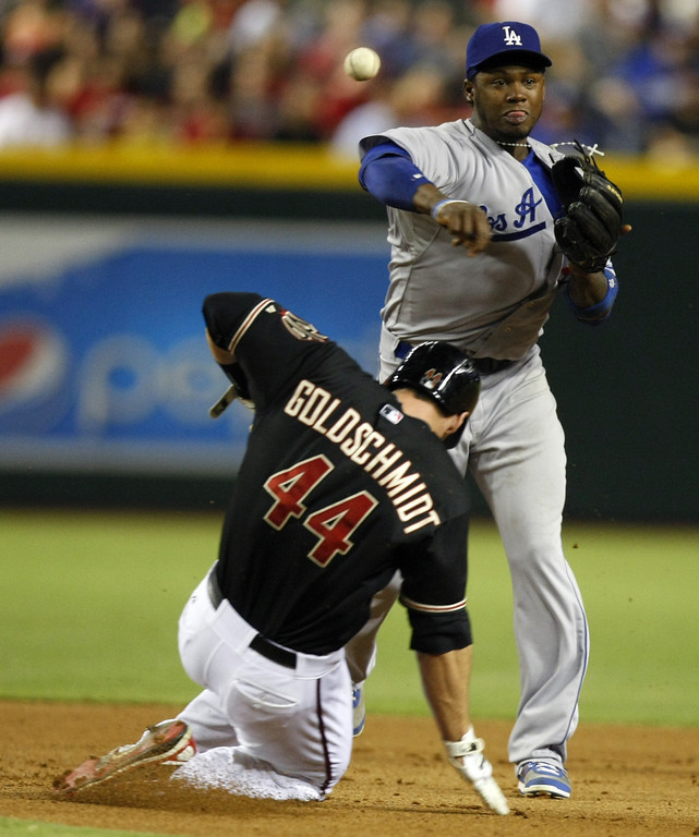 . Los Angeles Dodgers shortstop Hanley Ramirez (13), right, turns the double play while avoiding Arizona Diamondbacks\' Paul Goldschmidt (44) in the fourth inning during a baseball game on Monday, July 8, 2013, in Phoenix. (AP Photo/Rick Scuteri)