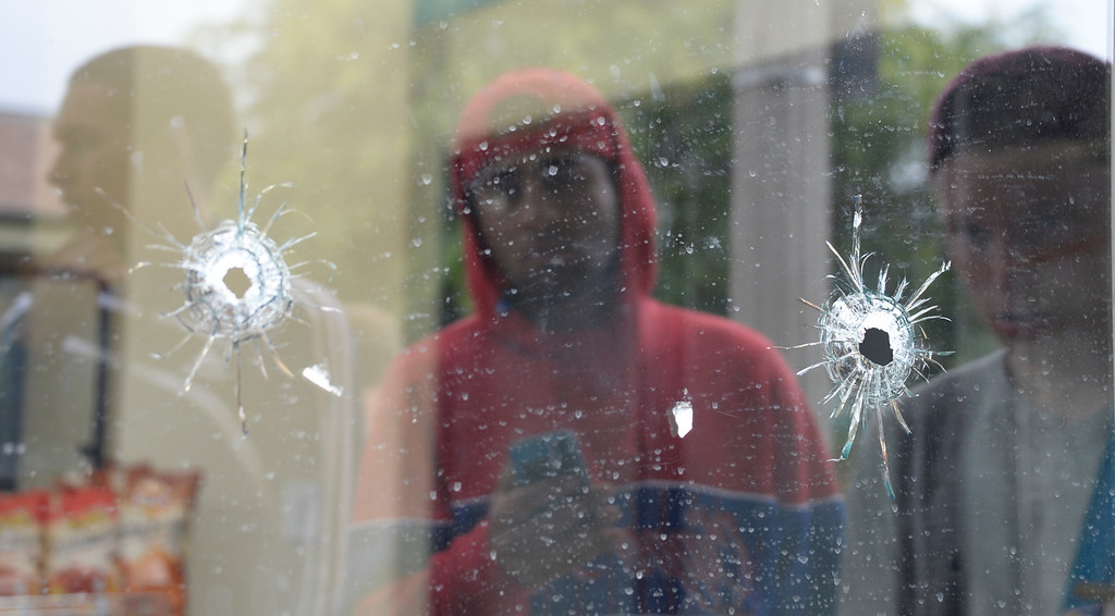 . May 24-,2014. Isla Vista, CA. UCSB students gather at IV Deli Mart where bullet holes are seen in the glass windows where one person was killed by the drive-by shooter Friday night. Seven people are dead, including the attacker, and seven others wounded, authorities said Saturday.