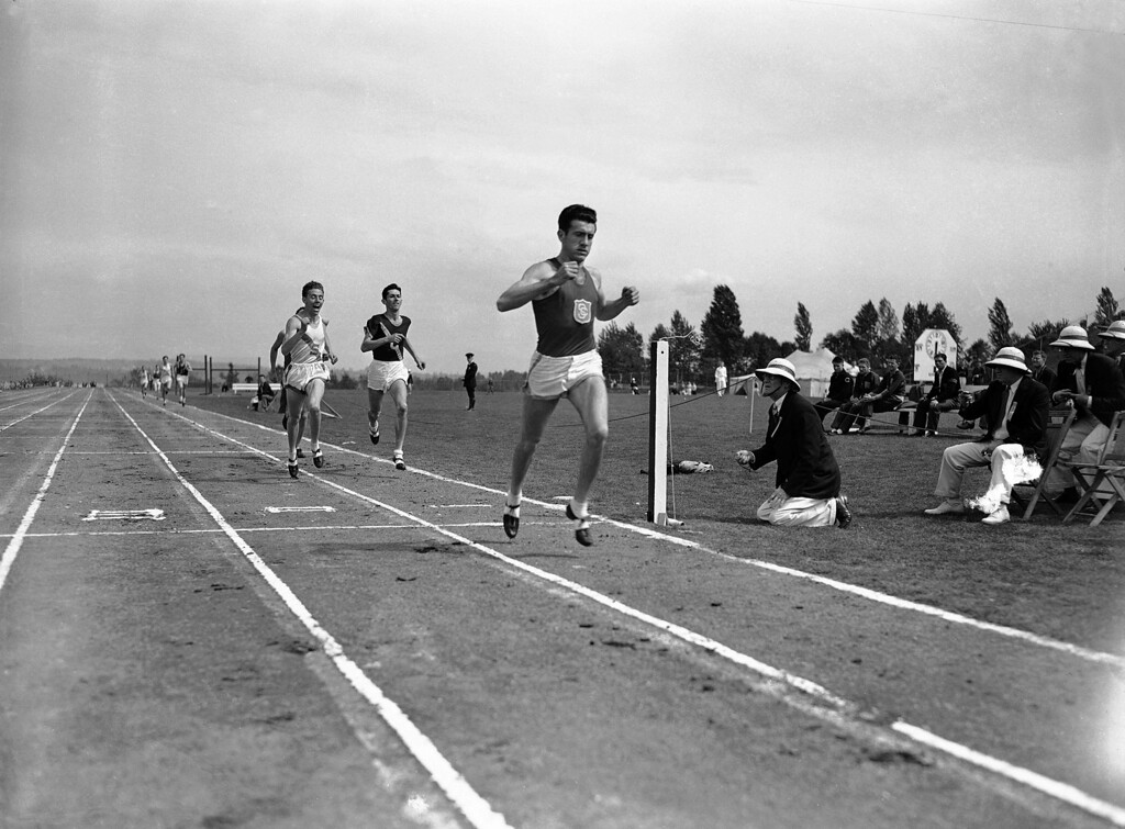 . FILE - In a May 20, 1939 file photo, Louis Zamperini of he University of Southern California, breaks the tape and record with a time of 4:16.3 to win the mile run in the Pacific Coast Conference Track and Field meet the University of Washington Stadium in Seattle. Leo Girard, of Stanford, left, was second and Cole, of California, second from left, was third. Zamperini, a U.S. Olympic distance runner and World War II veteran who survived 47 days on a raft in the Pacific after his bomber crashed, then endured two years in Japanese prison camps, died Wednesday, July 2, 2014, according to Universal Pictures studio spokesman Michael Moses. He was 97.  (AP Photo/Paul Wagner, File)
