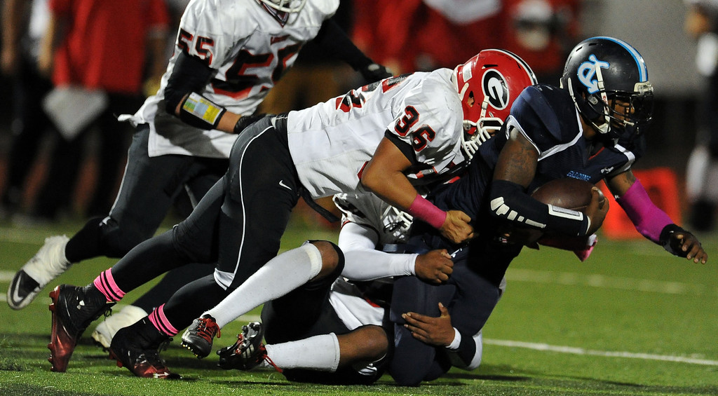 . Gladstone defense tackles Duarte\'s Sam Edwards for a loss of yards in the first half of a prep football game at Duarte High School in Duarte, Calif., Thursday, Oct. 10, 2013.    (Keith Birmingham Pasadena Star-News)