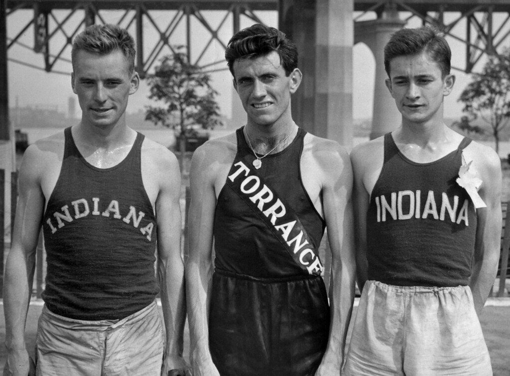 . FILE - In a July 13, 1936 file photo, Don Lash of Indiana, left, Louis Zamperini of Los Angeles, center, and Thomas Deckard of Indiana, who will represent the United States in the Olympic Games in the 5,000 meter team, at the Olympic tryouts in New York. Zamperini, a U.S. Olympic distance runner and World War II veteran who survived 47 days on a raft in the Pacific after his bomber crashed, then endured two years in Japanese prison camps, died Wednesday, July 2, 2014, according to Universal Pictures studio spokesman Michael Moses. He was 97.  (AP Photo, File)
