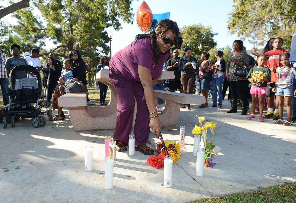 . Long Beach, Calif., -- 10-12-13- Pamela Huffman lights a candle at the spot where her sister and teacher Kellye Taylor,53, was fatally  stabbed in front of her students, at Orizaba Park  Friday October 11th 2013. Friends and family gathered at the park Saturday afternoon.    Stephen Carr/  Daily Breeze