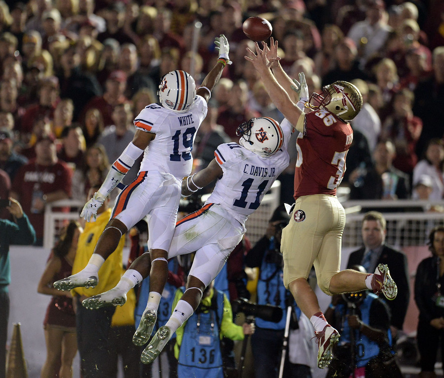 . Auburn\'s Ryan White (19) along with Auburn\'s Chris Davis (11) knocks away a ball intended for Florida State tight end Nick O\'Leary (35) in the first half of the BCS National Championship game at the Rose Bowl in Pasadena, Calif., on Monday, Jan. 6, 2014. 