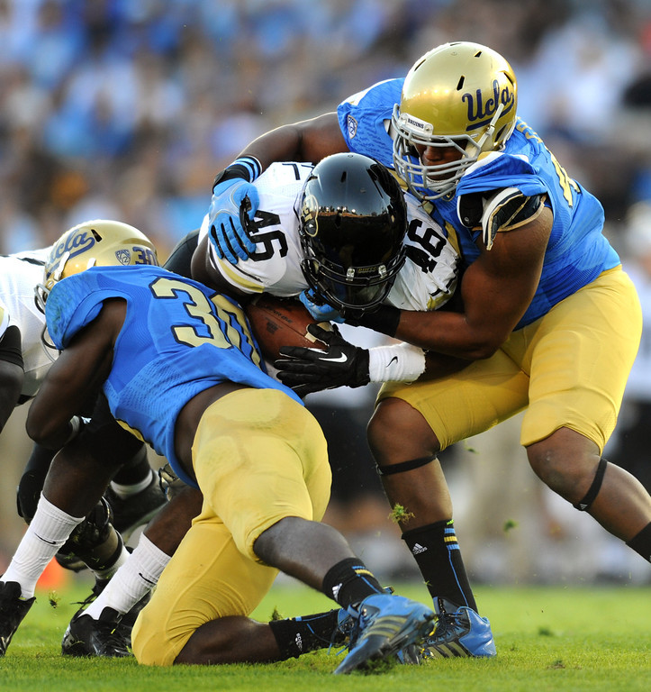 . UCLA\'s Myles Jack, left, and Keenan Graham stop Colorado RB Christian Powell in the first half, Saturday, November 2, 2013, at the Rose Bowl. (Photo by Michael Owen Baker/L.A. Daily News)