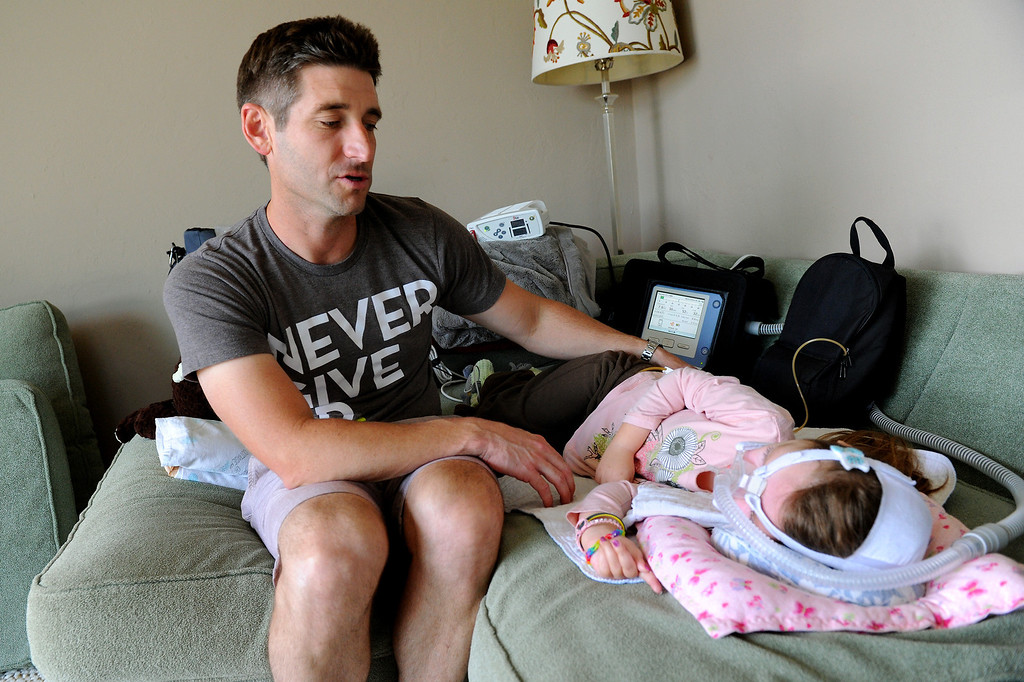 . Bill Strong talks to his daughter Gwendolyn on a sofa in their Santa Barbara home. Gwendolyn was born with spinal muscular atrophy. (Photo by Michael Owen Baker/Los Angeles Daily News)