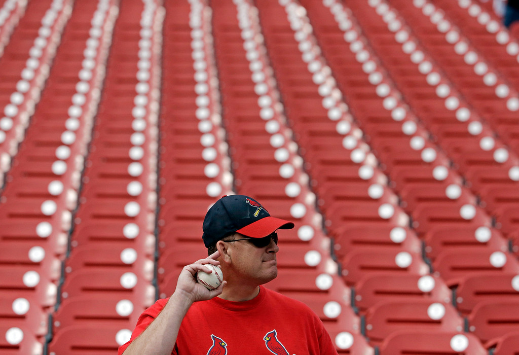 . A St. Louis Cardinals fan tries to listen to players during batting practice before Game 2 of the National League baseball championship series against the Los Angeles Dodgers Saturday, Oct. 12, 2013, in St. Louis. (AP Photo/Chris Carlson)