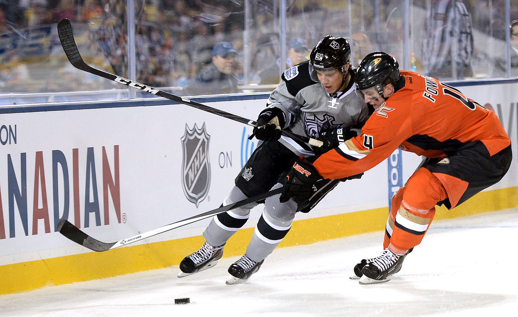 . Los Angeles Kings right wing Matt Frattin (21) chase the puck with Anaheim Ducks defenseman Cam Fowler (4) in the third period of the inaugural NHL Stadium Series game at Dodger Stadium in Los Angeles on Saturday, Jan. 25, 2014. Anaheim Ducks won 3-0. (Keith Birmingham Pasadena Star-News)