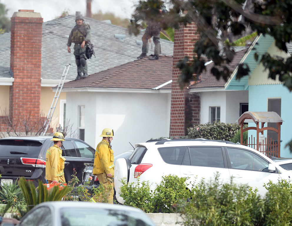 . Paramedics arrive to examin the suspect after El Monte SWAT Team members enter the home on the 11400-block of Elmcrest Street in El Monte finding the suspect dead after a standoff on Friday March 7, 2014. The suspect shot his neighbor over a dispute Friday morning. (Photo by Keith Durflinger/San Gabriel Valley Tribune)