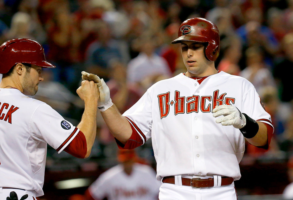 . Arizona Diamondbacks\' Paul Goldschmidt, right, gets a high-five from teammate A.J. Pollock after Goldschmidt connects for a two-run home run against Los Angeles Dodgers\' Hyun-Jin Ryu, of South Korea, in the first inning of a baseball game on Monday, Sept. 16, 2013, in Phoenix. (AP Photo/Ross D. Franklin)