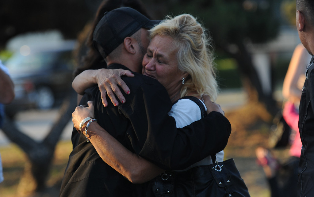 . Maria Montes, right, a family friend of the children is consoled in front of a make shift memorial for a Man and two children who were killed in a late Thursday night crash along the 3500 block of San Gabriel River Road on Friday, June 14, 2013 in Industry, Calif. Three others were injured in the crash.  (Keith Birmingham/Pasadena Star-News)