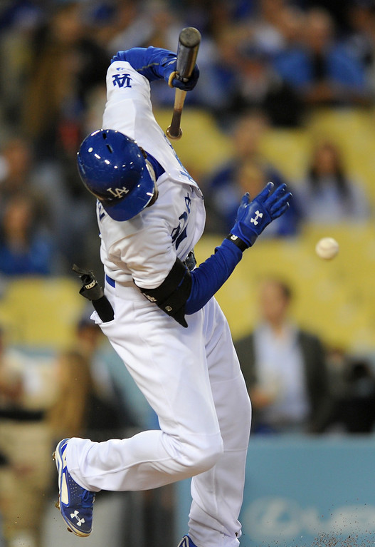 . The Dodgers Dee Gordon squirms out of the way after fouling off a bunt attempt against the Rockies, Friday, April 25, 2014, at Dodger Stadium. (Photo by Michael Owen Baker/L.A. Daily News)