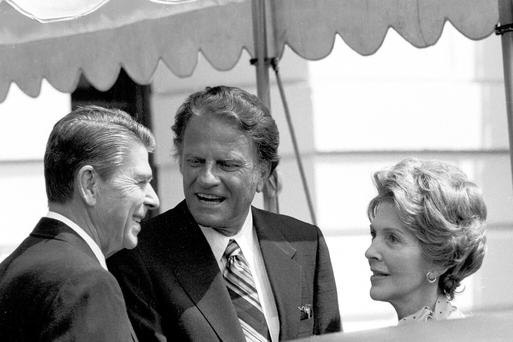 . The Reverend Billy Graham, center, talks with President Ronald Reagan, left, and first lady Nancy Reagan at the White House July 18, 1981. (AP Photo/J. Scott Applewhite)