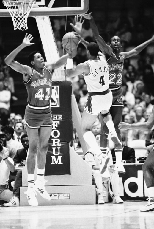 . Byron Scott (4) of the Los Angeles Lakers shoots through the outstretched arms of Sam Perkins (41) and Rolando Blackman of the Dallas Mavericks in early Playoff Action on Wednesday night, April 30, 1986 at the Forum in Inglewood. (AP Photo/Michael Tweed)