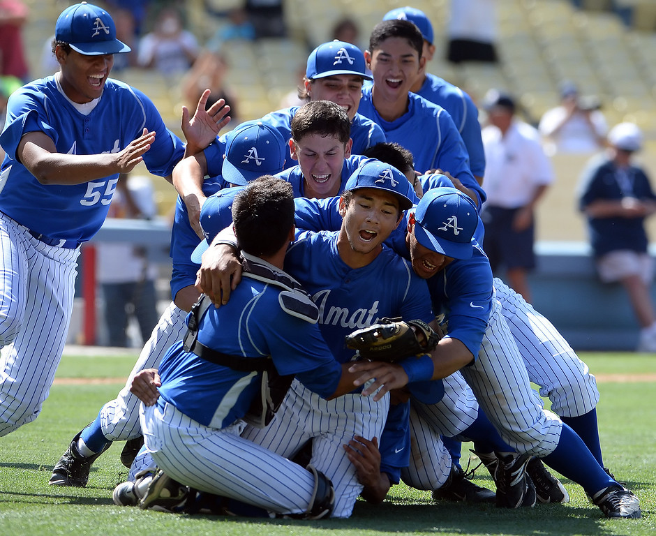 . Bishop Amat pitcher Scott Hurst, center, is mobbed by teammates after recording the final out and defeating Palm Desert 4-3 to win the CIF-SS Division 3 baseball championship at Dodger Stadium in Los Angeles on Friday, June 6, 2014. 