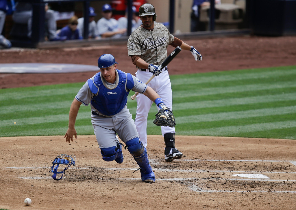 . Los Angeles Dodgers catcher Tim Federowicz chases down a wild pitch as a San Diego Padres\' baserunner advances during the second inning of a baseball game in San Diego, Sunday, June 23, 2013. The Padres batter is Jesus Guzman.  (AP Photo/Lenny Ignelzi)