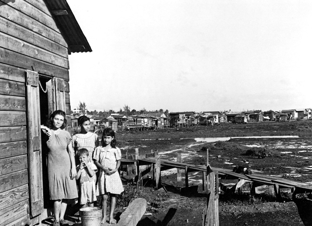 ". A family is seen outside of their wooden home in the slum area known as ""El Fanguito\"" or \""The Mud\"" in San Juan, Puerto Rico in this January 1942 photo.   (AP Photo/Library of Congress, Jack Delano)"