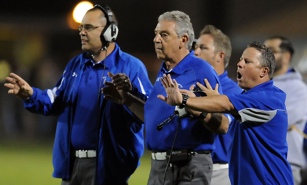 . Charter Oak head coach Lou Farrar, center ,and coach Dom Farrar, left, and coaching staff in the first half of a prep football game against South Hills at Covina DIstrict Field in Covina, Calif., on Thursday, Oct. 24, 2013. 