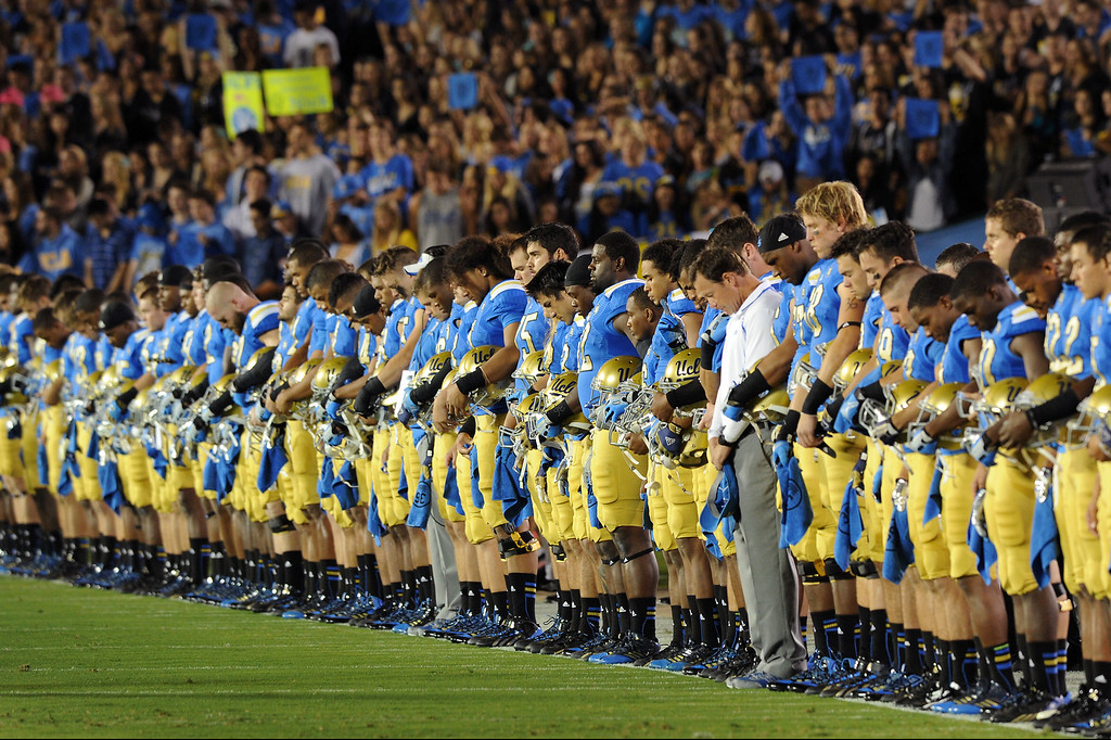 . The UCLA team stands for a moment of silence before their game against New Mexico State, Saturday, September 21, 2013, at the Rose Bowl, to honor teammate Nick Pasquale who was killed when struck by a car September 8. (Photo by Michael Owen Baker/L.A. Daily News)