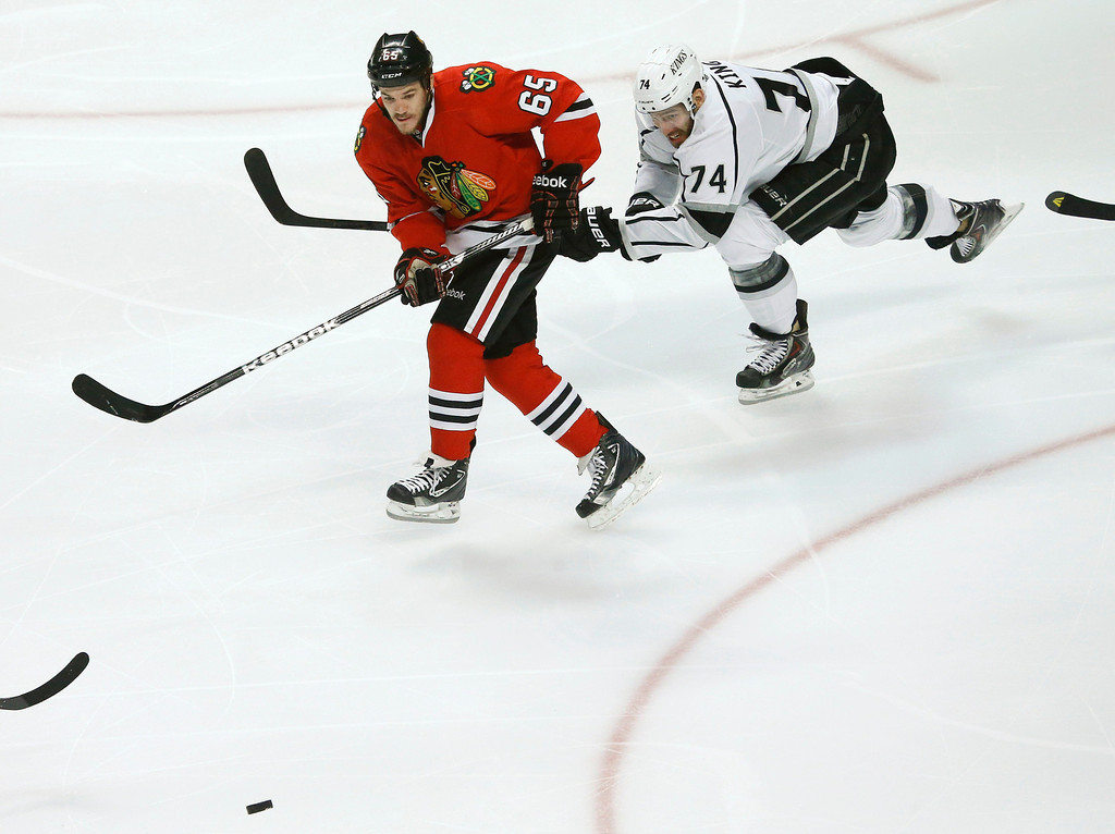 . Chicago Blackhawks center Andrew Shaw (65) takes a pass as Los Angeles Kings center Dwight King (74) defends during the first period in Game 2 of the NHL hockey Stanley Cup Western Conference finals Sunday, June 2, 2013 in Chicago. Shaw scored on the play. (AP Photo/Charles Rex Arbogast)