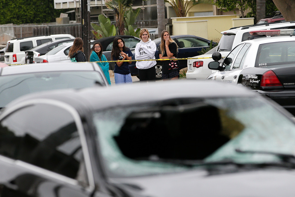 . Onlookers gather near a black BMW sedan driven by a drive-by shooter on Saturday, May 24, 2014, in Isla Vista, Calif. The shooter went on a rampage near a Santa Barbara university campus that left seven people dead, including the attacker, and seven others wounded, authorities said Saturday. (AP Photo/Jae C. Hong)