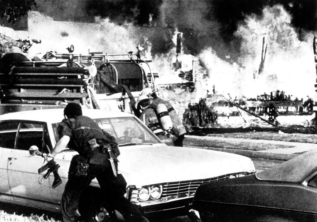 . A police officer carrying an automatic weapon gets into position to protect firefighters on May 17, 1974 as police attack a Symbionese Liberation Army hideout near Watts.      (Los Angeles Daily News file photo)