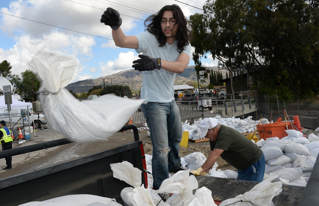 . Christopher Serrano loads up sandbags with his father, Ramiro, at the Glendora City Yard as they plan to block off their driveway on Thursday February 27, 2014. (Staff Photo by Keith Durflinger/San Gabriel Valley Tribune)