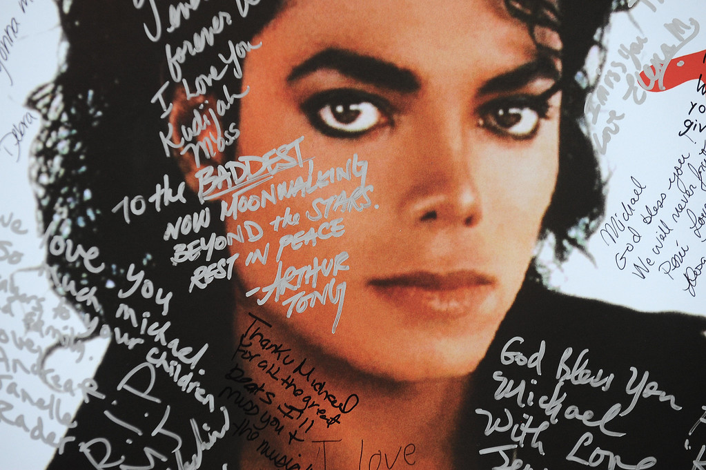 """. A poster of Michael Jackson is covered with messages from fans at a one-day tribute to the \""""King of Pop\"""" which included outdoor screenings of \""""The Wiz\"""" and \""""Thriller\"""" at Universal CityWalk in Universal City, California on July 9, 2009.  (ROBYN BECK/AFP/Getty Images)"""