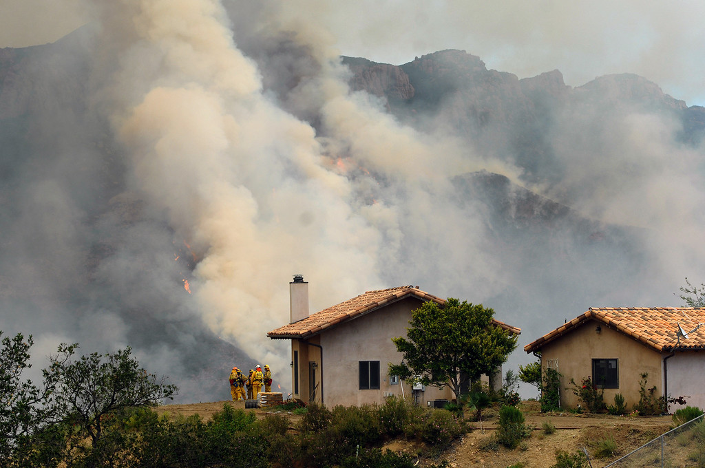 . Monrovia fire personnel guard a house on Deer Creek Road as a hillside flares up in Ventura County, Friday, May 3, 2013. (Michael Owen Baker/Los Angeles Daily News)