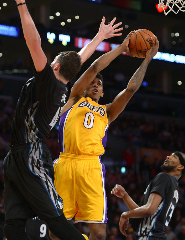 . The Lakers\' Nick Young goes to the rim past the Timberwolves\' Kevin Love in the first half, Friday, December 20, 2013, at Staples Center. (Photo by Michael Owen Baker/L.A. Daily News)