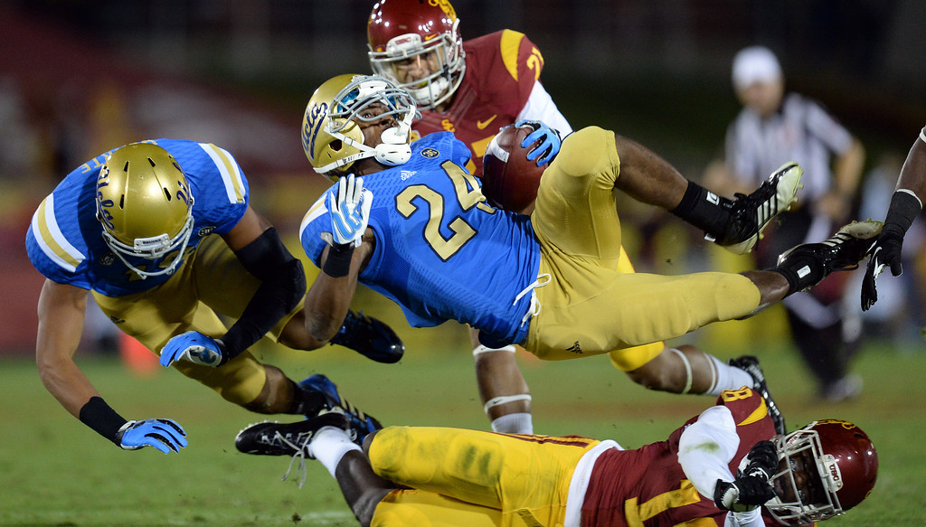 . UCLA�s Paul Perkins #24 is upended by USC�s Dion Bailey #18 during their game at the Los Angeles Memorial Coliseum Saturday, November 30, 2013.  (Photo by Hans Gutknecht/Los Angeles Daily News)