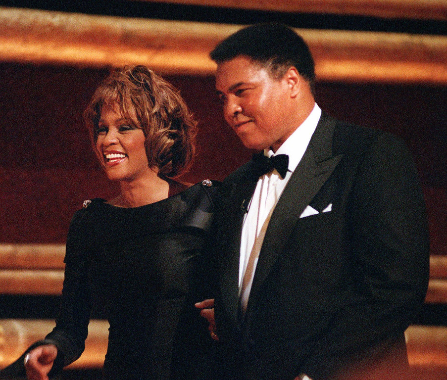 """. Former World Heavyweight Boxing Champion Muhammad Ali is greeted by singer Whitney Houston as he arrives on stage at New York\'s Radio City Music Hall to accept a GQ \""""Men of the Year\"""" Award Wednesday, Oct. 21, 1998.   (AP Photo/Mitch Jacobson)"""
