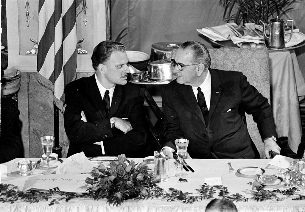 . Evangelist Billy Graham, left, chats with President Lyndon B. Johnson at the annnual prayer breakfast in Washington, D.C., February 5, 1964.  (AP Photo)