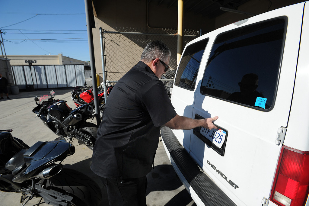 . TRAP team supervisor, Detective Jess Corral opens the back of a van that was used to steal motorcycles. The windows were painted black so that you could not see inside. The Taskforce for Regional Autotheft Prevention just broke up a high-end theft/chop shop motorcycle ring. The bikes are parked in a tow yard in North Hollywood, CA. 12/20/2013, photo by (John McCoy/Los Angeles Daily News)