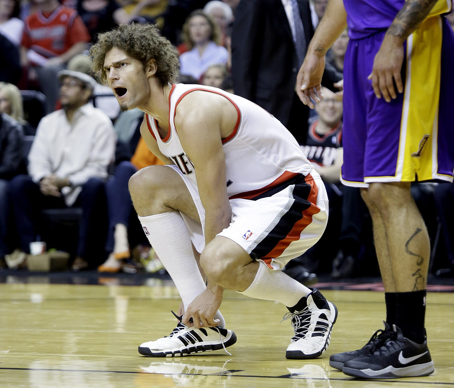. Portland Trail Blazers center Robin Lopez complains to the referee as he  puts his shoe back on during the second half of an NBA basketball game against the Los Angeles Lakers in Portland, Ore., Monday, March 3, 2014.(AP Photo/Don Ryan)