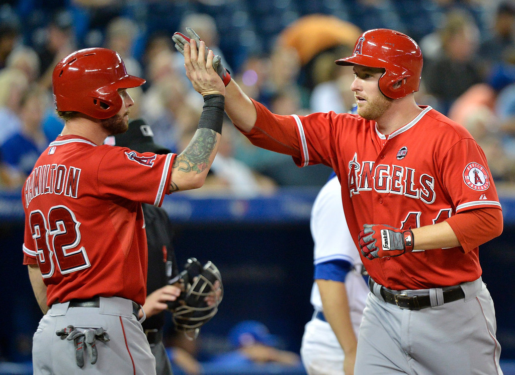 . Los Angeles Angels\' Mike Trumbo, right, celebrates his two-run home run with teammate Josh Hamilton, left, during second-inning AL baseball game action in Toronto, Wednesday, Sept. 11, 2013. (AP Photo/The Canadian Press, Nathan Denette)