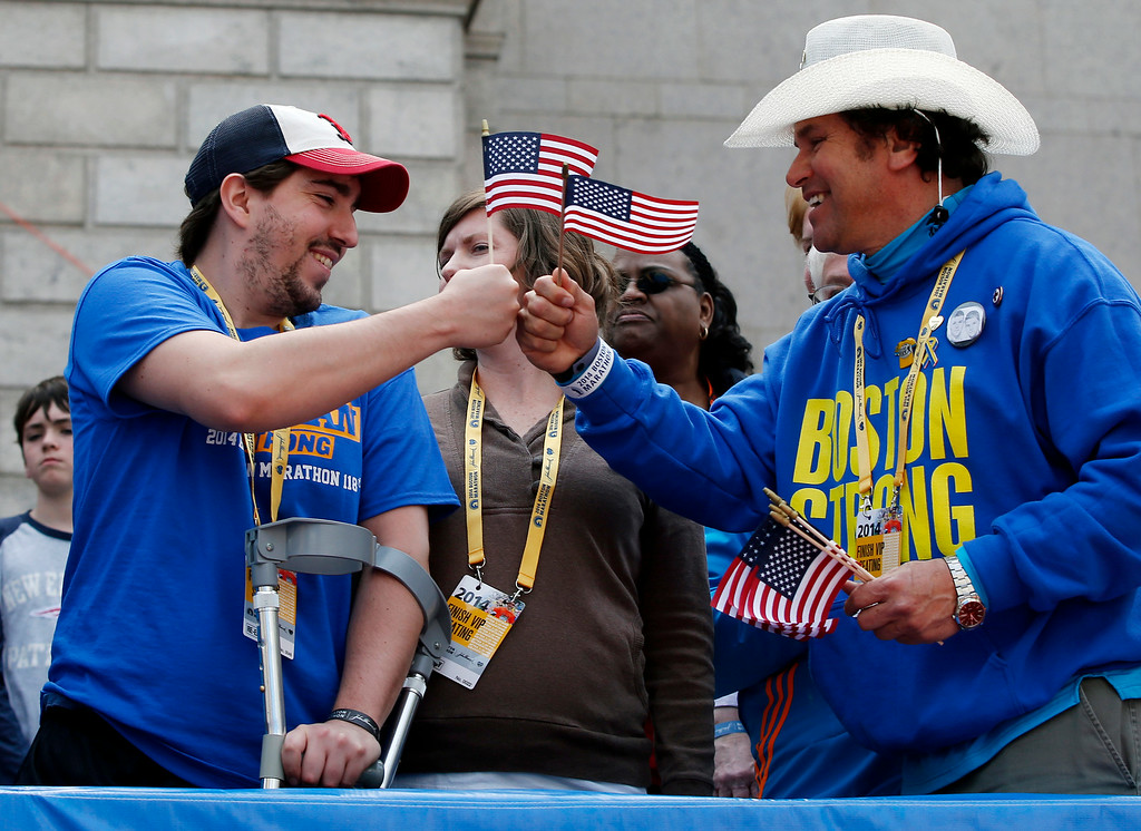 . Holding American flags, Boston Marathon bombing survivor Jeff Bauman, left, bumps fists with Carlos Arredondo near the finish line of the the 118th Boston Marathon, Monday, April 21, 2014, in Boston. (AP Photo/Elise Amendola)