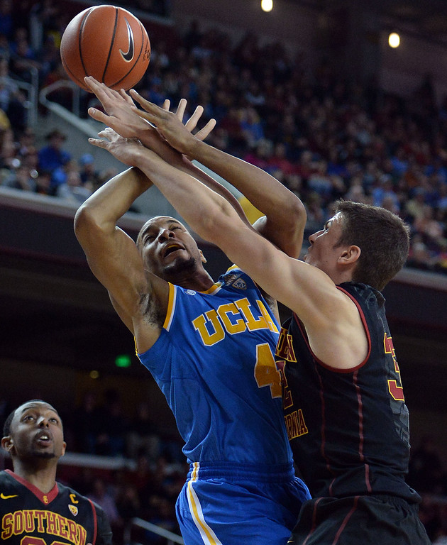 . UCLA\'s Norman Powell (4) is fouled by Southern California\'s Nikola Jovanovic (32) in the first half of a PAC-12 NCAA basketball game at Galen Center in Los Angeles, Calif., on Saturday, Feb. 8, 2014. (Keith Birmingham Pasadena Star-News)